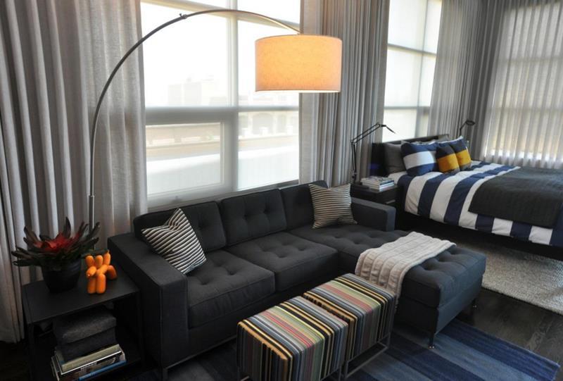 Amenajare in stil masculin - garsoniera cu mobilier minimalist: canapea gri, taburete in dungi colorate