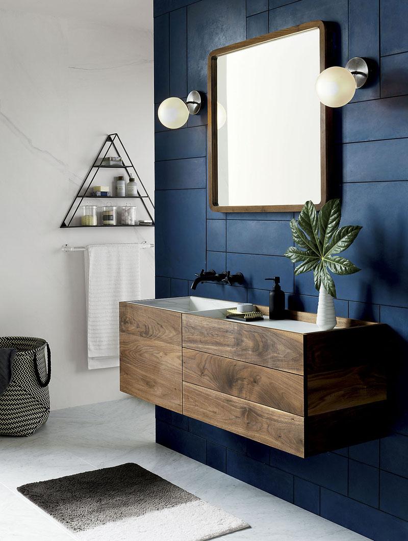 Perete albastru de baie cu masca de chiuveta din lemn si oglinda