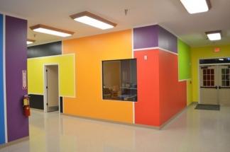 Amenajare hol scoala gradinita cu pereti in portocaliu, mov, rosu