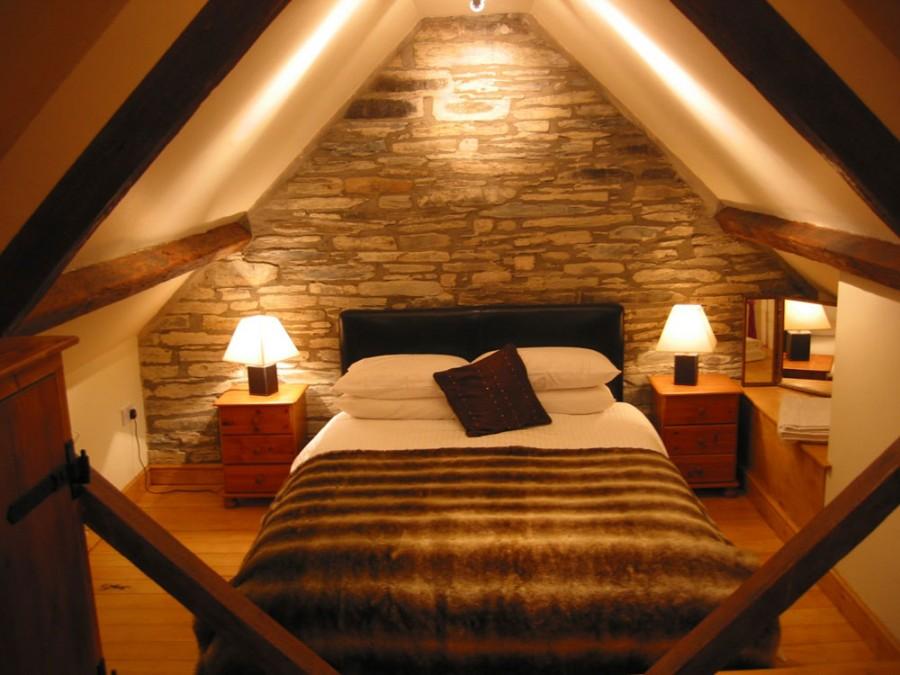Dormitor amenajat la mansarda cu mobilier rustic din lemn