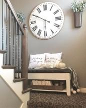 Amenajare hol cu locuri de sedere cu bancheta din lemn, perne deco si ceas vintage