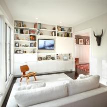 Amenajarea unui living mic - canapea alba, perete cu rafturi